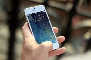 Bilden visar en hand som håller i en telefon